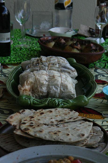 Midde-Oosters-Mediterreens-gedekte tafel met uie wat hul glorie onthul langs skaapboud in perkamentpapier en sumac-platbrode.