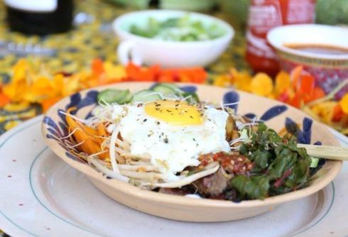 Bibimbap bestaan uit rys wat omring word met bykosse, piekels, rooisous en 'n gebakte eier.